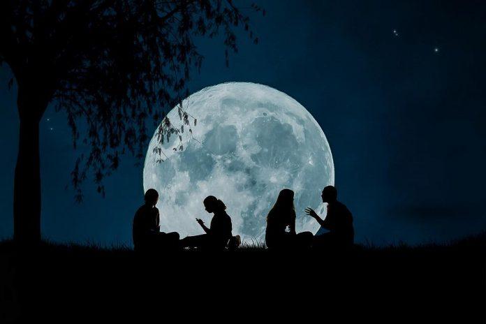Ludzie siedzący na trawie, na tle Księżyca