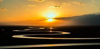 Zachodzące słońce nad rzeką rozlewającą sie po równinie-ciekawy Quiz o rzekach świata