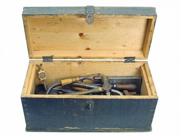 Stara drewniana skrzynka warsztatowa w kolorze niebieskim, w środku stare narzędzia
