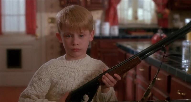Macaulay Culkin w filmie Kevin sam w domu, trzyma strzelbę, czeka na rabusi, scena z komedii