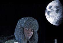 Facet wznoszący toast kieliszkiem wódki, w tle góry i księżyc