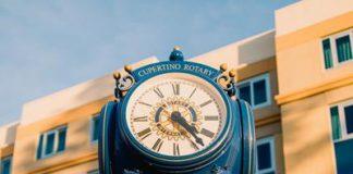 Stary, niebieski zegar uliczny, z rzymskimi liczbami, stojący na tle budynku. Quiz o rzymskich liczbach
