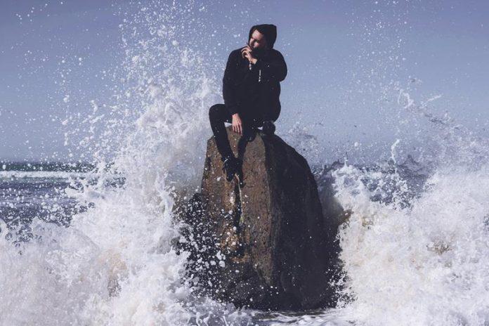 Człowiek siedzący na skale pośród sztormu