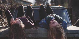 dziewczyny leżące na starym samochodzie