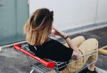 Dziewczyna siedząca w sklepowym wózku