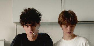 Dwóch chłopaków, jeden pali papierosa, drugi je płatki