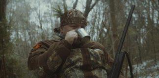 Myśliwy przy ognisku pije wódkę z kubka, śmieszne zdjęcie z polowania