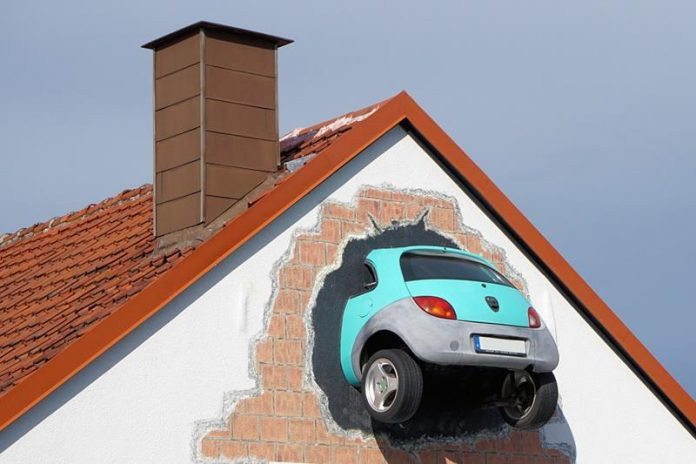 Mural, instalacja artystyczna, samochód w ścianie budynku