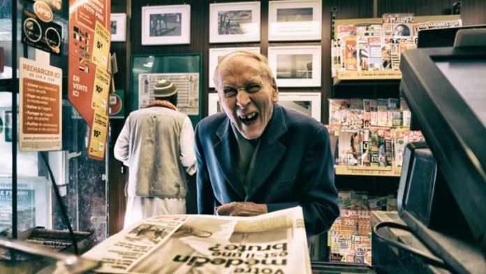 Uśmiechnięty starszy pan w garniturze wybiera gazetę w saloniku prasowym