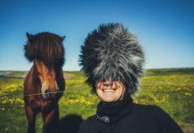 Facet w futrzanej czapce, obok koń z obfitą grzywą
