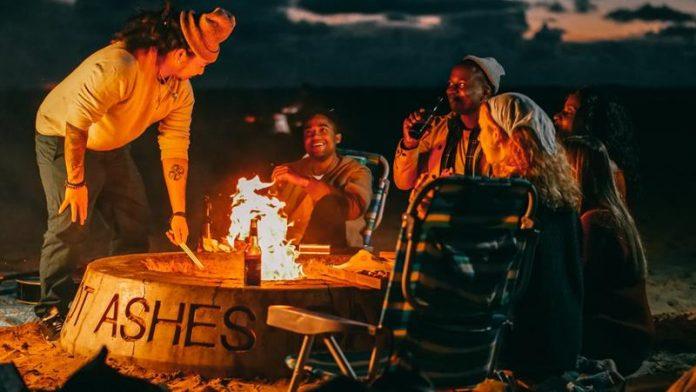 Grupa przyjaciół pije piwko przy ognisku