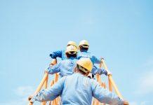 robotnicy w kaskach ochronnych idący do pracy